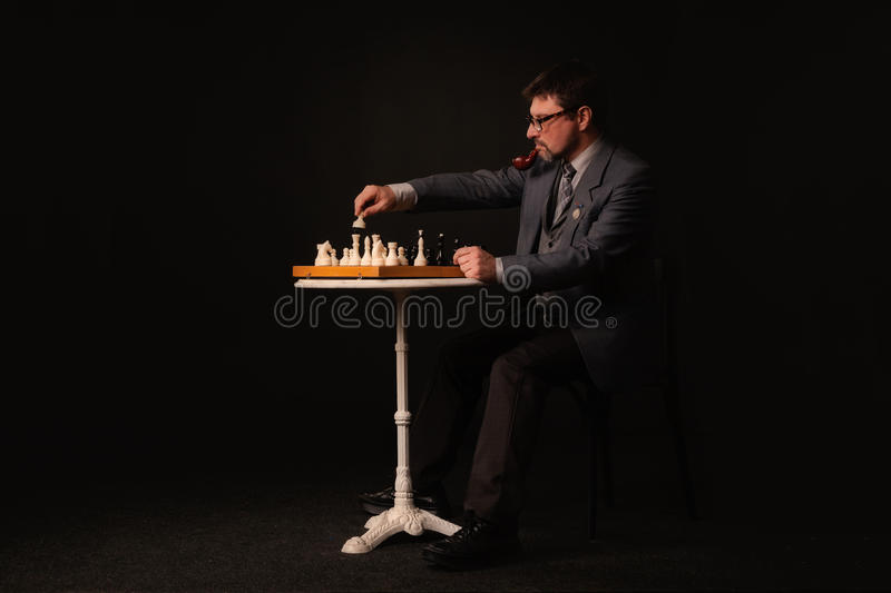 A man plays chess and smokes a pipe on a dark background stock photo