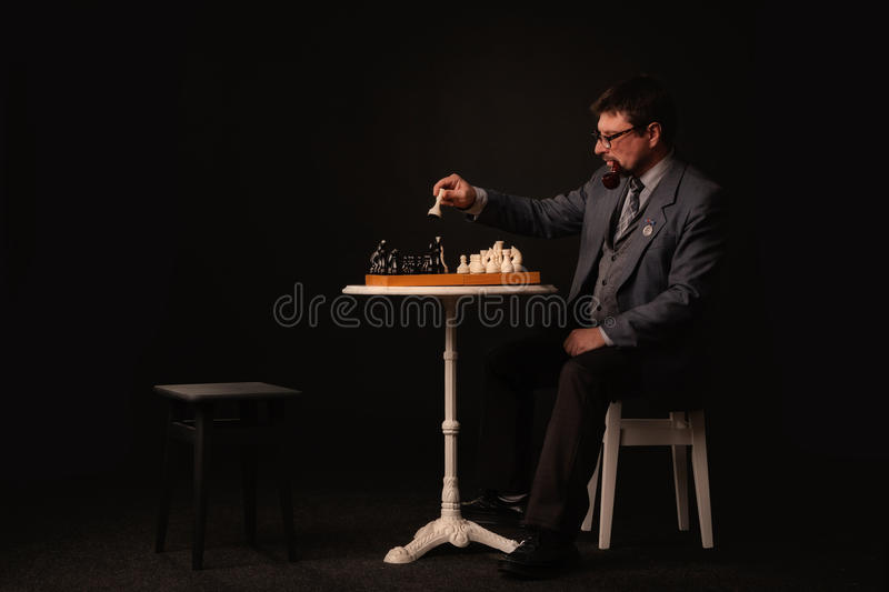 A man plays chess and smokes a pipe on a dark background royalty free stock image