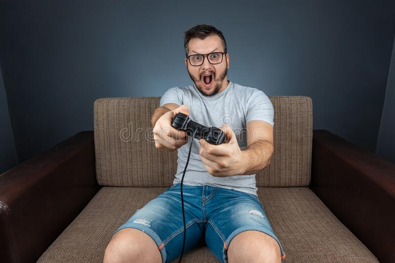 A man plays the console, video games react strongly and emotionally while sitting on the couch. Day off, entertainment, leisure royalty free stock photography