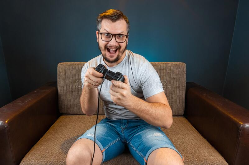 A man plays the console, video games react strongly and emotionally while sitting on the couch. Day off, entertainment, leisure.  royalty free stock image