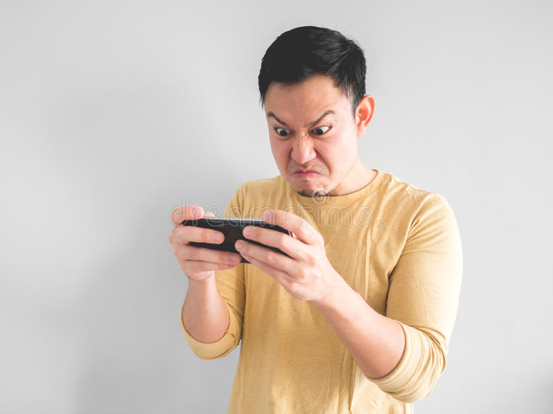 Man plays game furiously. Angry Asian man plays mobile game on his smartphone stock photography
