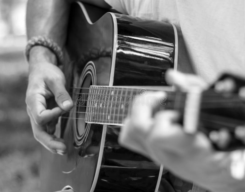 Man plays guitar in black and white tones royalty free stock image