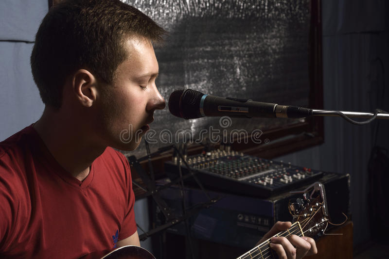 Man plays guitar and sings stock photography