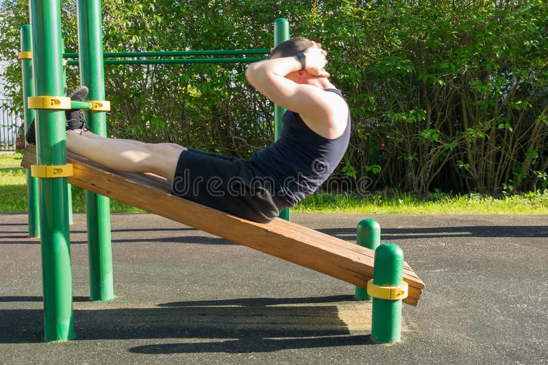 A man plays sports on the site, does exercises to strengthen the press. A man plays sports on the site,  does exercises to strengthen the press royalty free stock photography