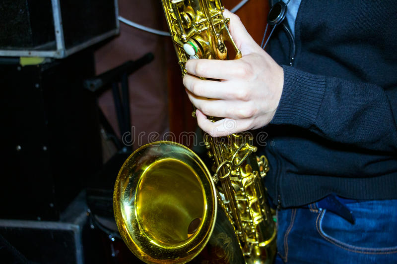 Man plays a tenor sax. Golden color royalty free stock photo