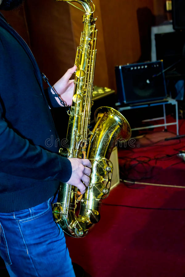 Man plays a tenor sax. Golden color royalty free stock photography