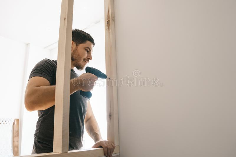 The man is pleased with the screwdriver, fixing the wooden frame for the window to the light wall. Repair yourself stock image
