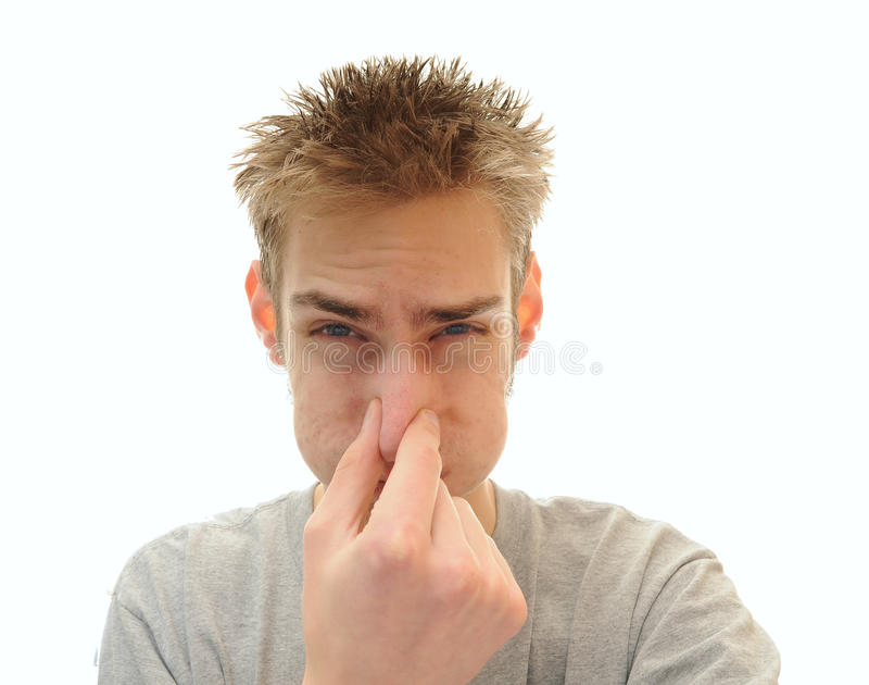 Man plugging his nose from odor. Young adult man tightly holds his hand over his nose in order to plug out the horrible odor he is smelling. Isolated on white stock image