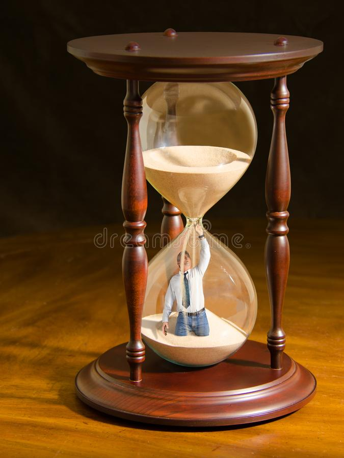 Man plugging hole inside hour glass trying to slow the flow of sand and stop time. Man plugging hole inside an hour glass trying to stop the sand from flowing stock image