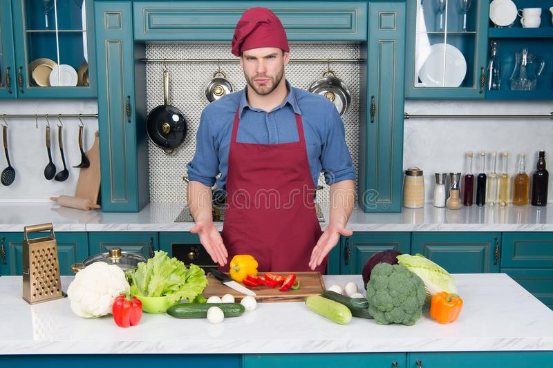 Man point at vegetables on table. Cook in chef hat and apron in kitchen. Ingredients for cooking dishes. Vegetarian menu and healt stock photography