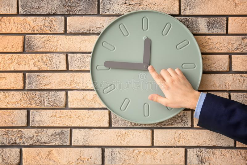 Man pointing on clock against wall background. Time management concept stock photography