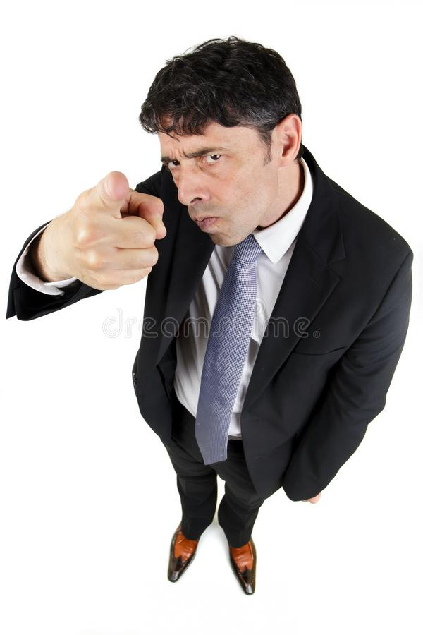 Man pointing a finger in accusation. Humorous high angle portrait of a man in a business suit pointing a finger in accusation and blame with a stern royalty free stock image