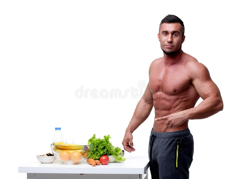 Man pointing at healthy food. Handsome muscular man pointing at healthy food stock photos