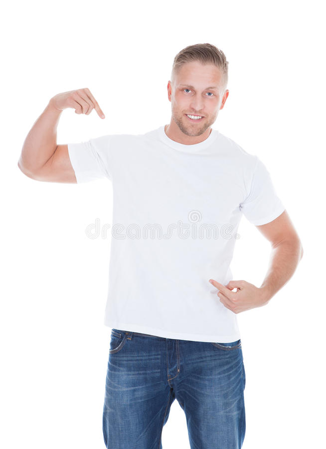 Man pointing at his blank white t-shirt. Photo of a muscular man pointing his fingers at the front of at his blank white t-shirt with copyspace for your text or stock photo