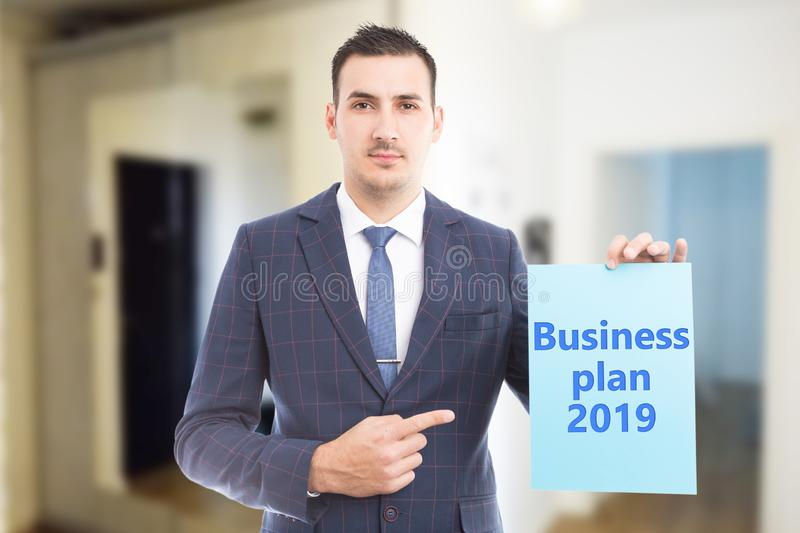 Man pointing at paper with business plan for year stock photo