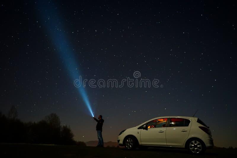 Man pointing at stars. Man pointing flashlight at sky full of stars at night