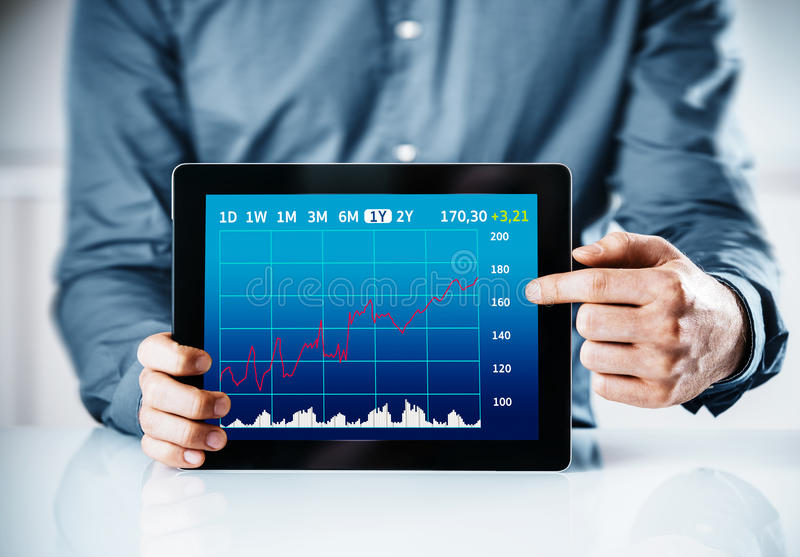 Man pointing to a business graph on a tablet. Displaying a monthly time line and statistics or projections in an analysis or presentation concept stock photography