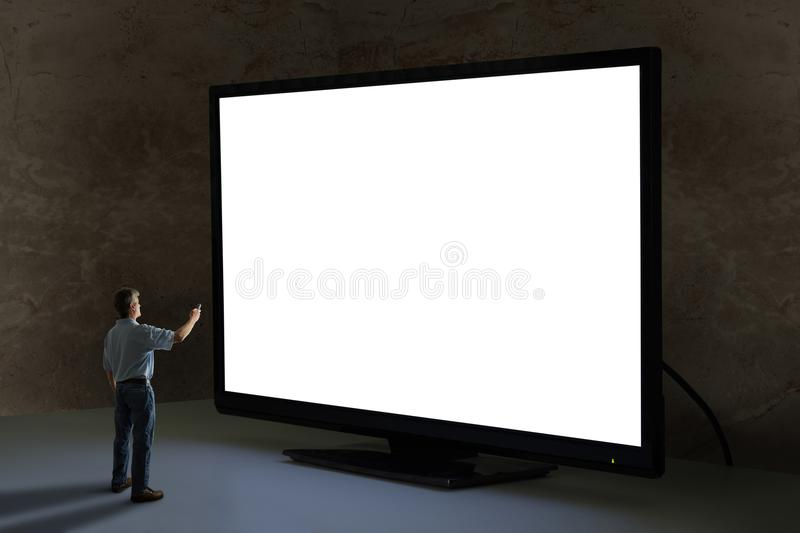 Man pointing tv remote control at world's biggest giant television with blank screen stock photography
