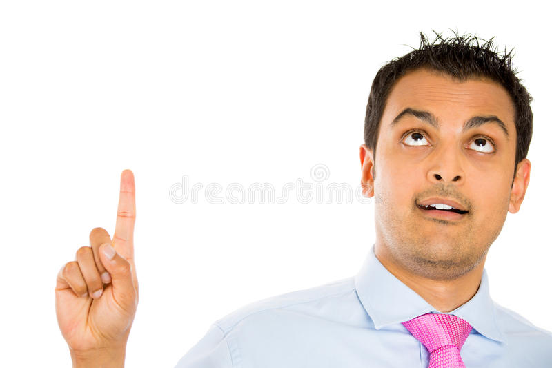 Man pointing up. Closeup portrait of goofy, idiot, lamebrain, numbskull, nerd, geek, looking and pointing up, isolated on white background stock image