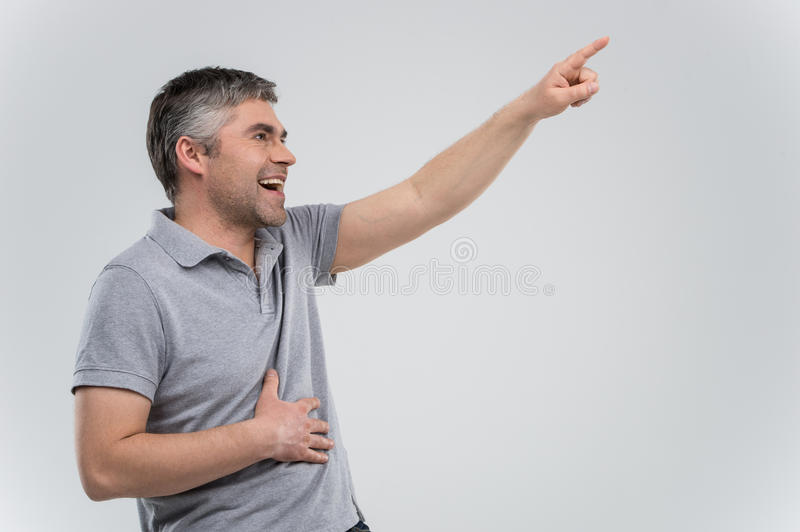 Man pointing up and laughing on grey background. stock photos
