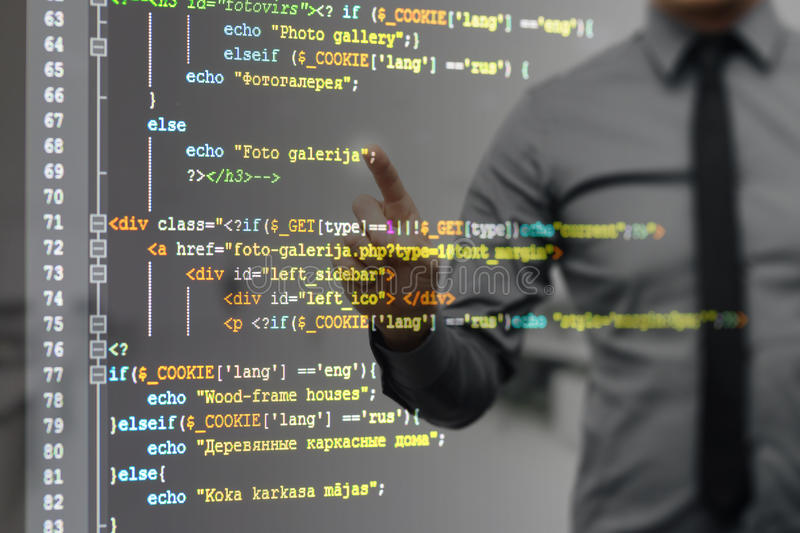 Man pointing on virtual screen with website programming code. Man pointing on virtual screen with colorful website programming code royalty free stock images
