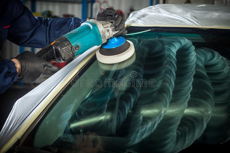 MAn polishes the front glass. Close-up of a male mechanic with a blue prism and protective gloves polishes the front glass of the car with a modern green royalty free stock photo
