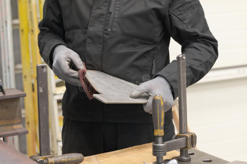 Man polishing metal part of product. During working process with gloves stock photo