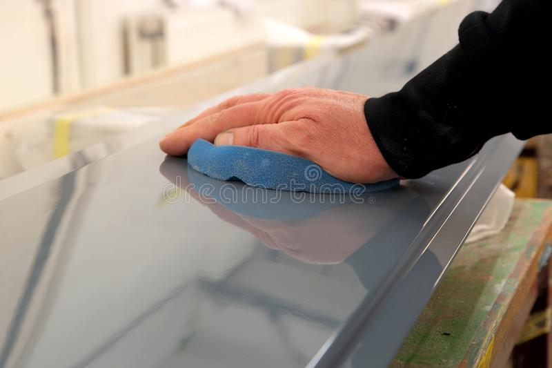 Man polishing a painted metal panel with a blue foam pad stock image