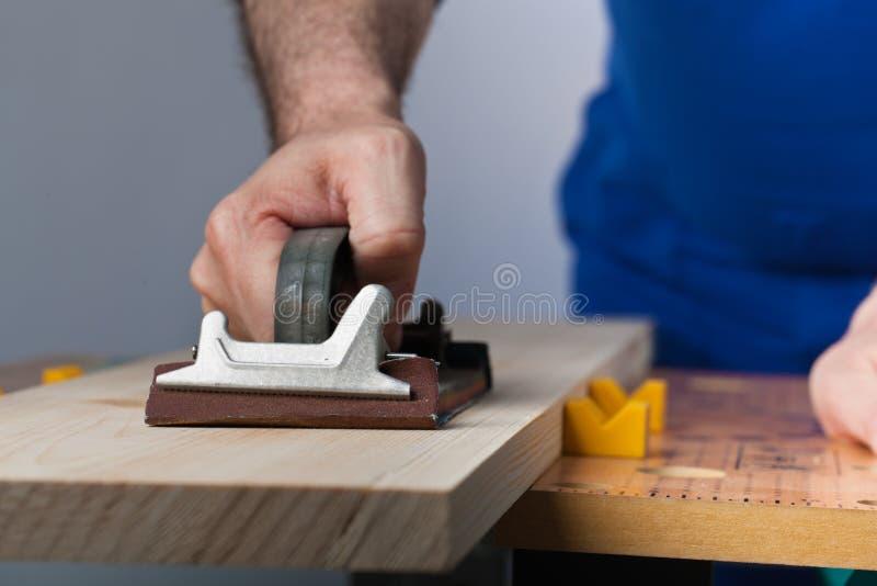 Polishing wooden plank royalty free stock photography