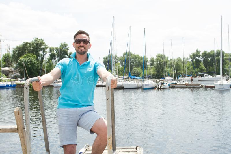 Bearded Man in polo and sunglasses laddering up on boat. Happy businessman on vacation with yachts on dock. Man in polo and sunglasses laddering up on boat royalty free stock photos