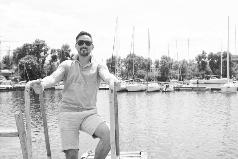 Man in polo and sunglasses laddering up on boat. Happy businessman on vacation with yachts on dock and wooden pier background. Man in polo and sunglasses stock images