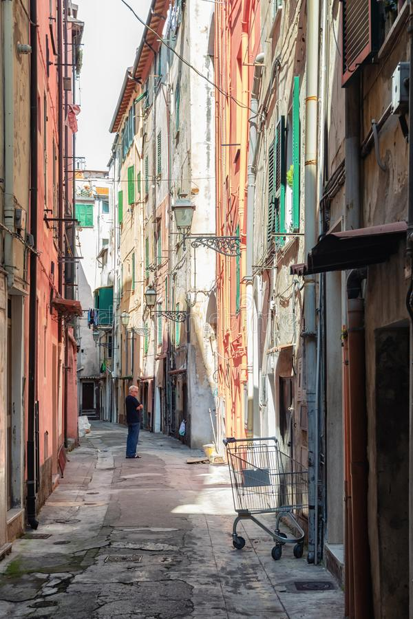 Man is pondering in the narrow street Via Bezzecca in the center of the Italian town San Remo royalty free stock photography