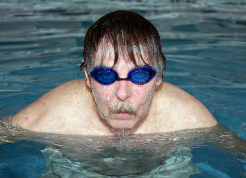 Man in pool. Close up portrait of a senior athlete in a swimming pool wearing goggles stock photography