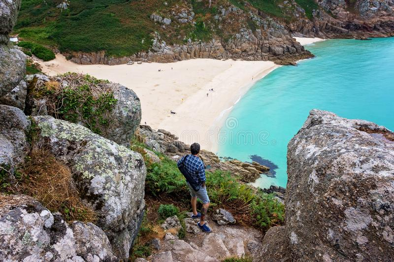 Man in Porthcurno beach view stock images