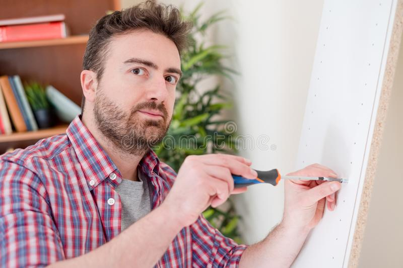 Man portrait and do it yourself furniture assembly. New home and man assembling furniture do it yourself royalty free stock image
