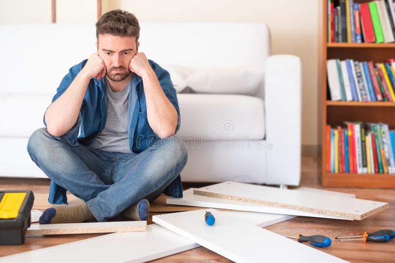 Man portrait and do it yourself furniture assembly. Sad young man reading the instructions to assemble furniture royalty free stock image