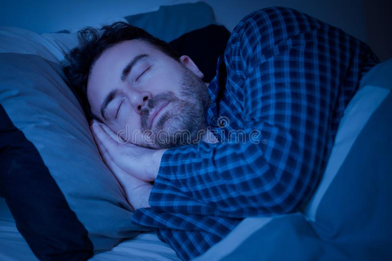 Man portrait sleep comfortable and feeling good. Man sleeping portrait in bed at night royalty free stock photography