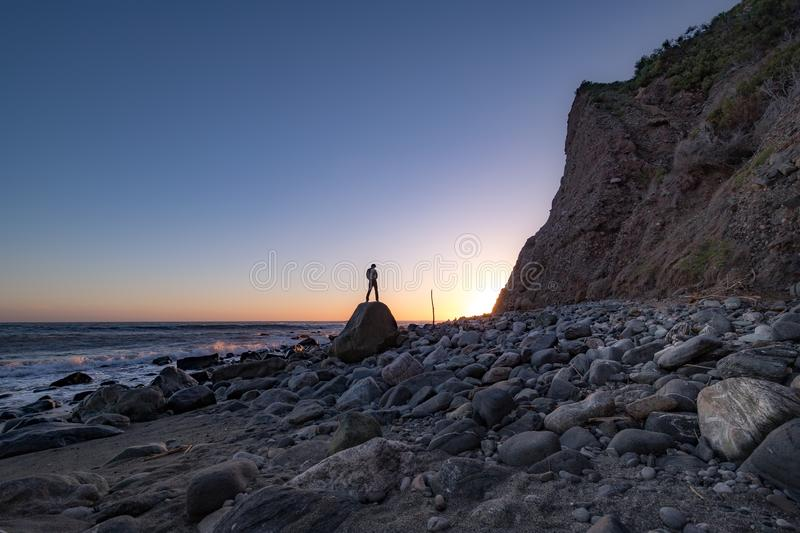 Man Posed on a Rock at Sunset. Beachside view of a man posed on a rock near a tall cliff as the sun approaches the horizon, Dana Point, California royalty free stock image