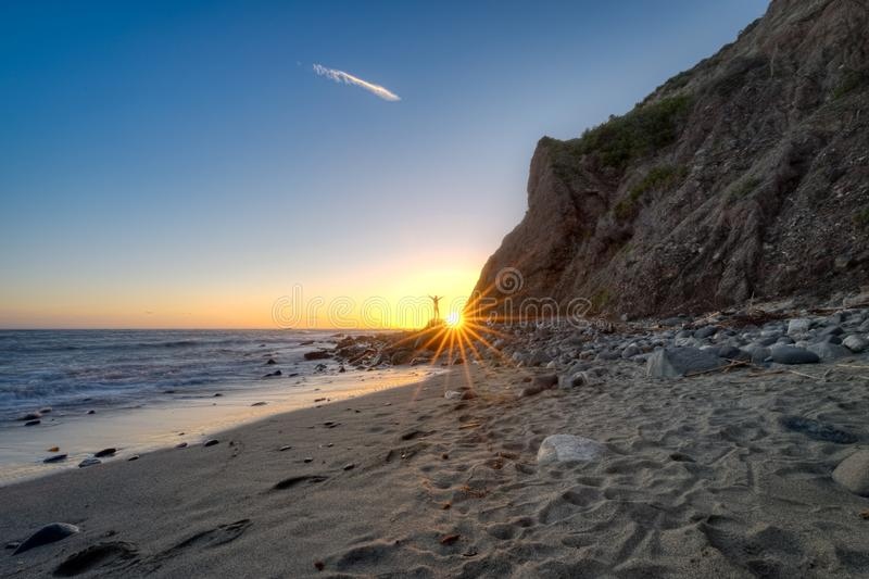 Man Posed on a Rock at Sunset. Beachside view of a man posed on a rock near a tall cliff as the sun approaches the horizon, Dana Point, California stock images