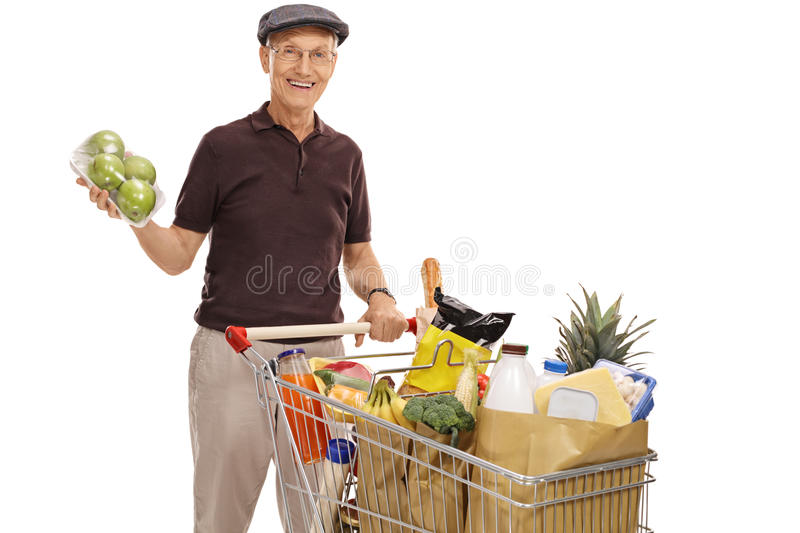 Man posing with an apple pack and shopping cart. Cheerful elderly man posing with a pack of apples and a shopping cart full of groceries isolated on white royalty free stock image