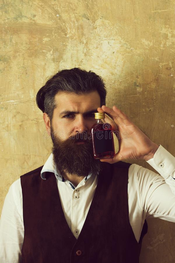 Man posing with bottle of red liqueur. Bearded hipster with long beard, moustache and stylish hair on beige wall. Alcohol, appetizer and aperitif. Addictive stock image