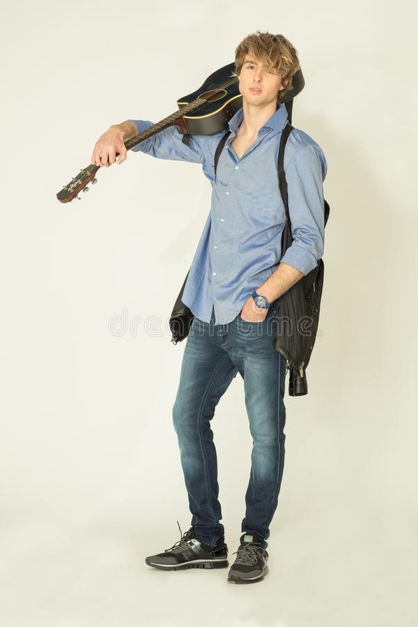 Man posing on  with guitar on light background royalty free stock image
