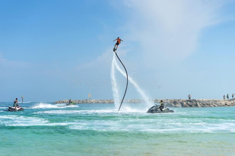 Man posing at new flyboard at Caribbean tropical beach. Positive stock photo