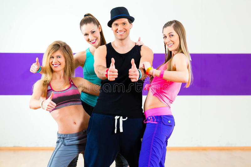 Man posing with woman in dance school. Man posing with women in zumba dance school stock image