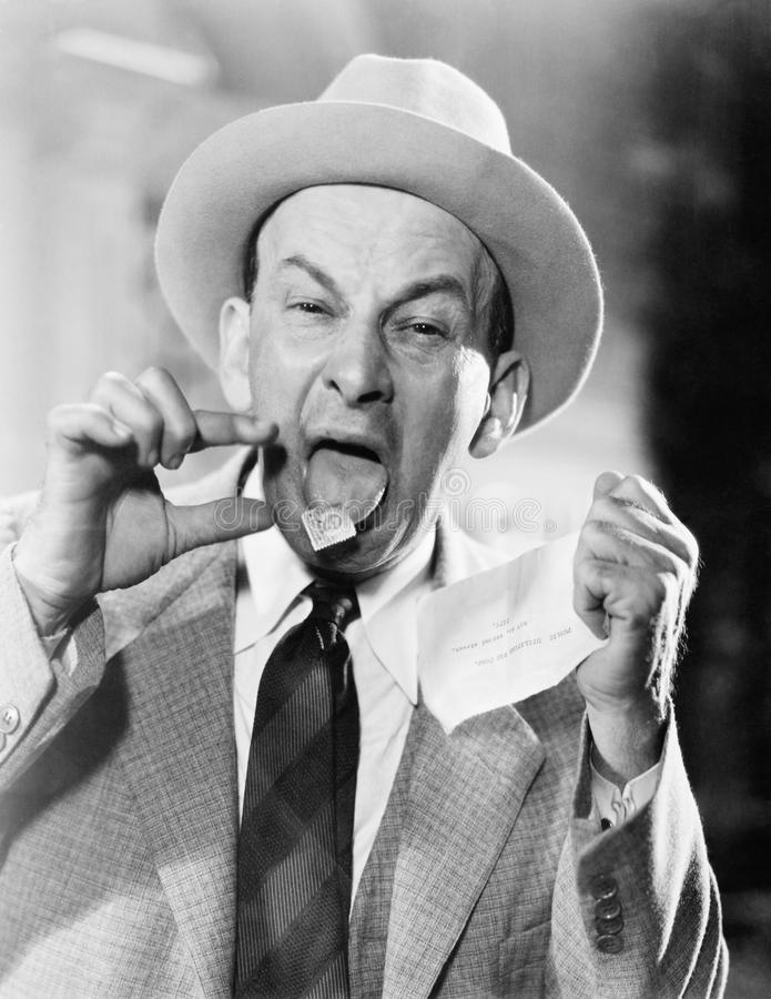 Man with a postage stamp stuck on his tongue royalty free stock image