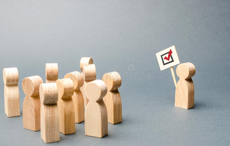 A man with a poster agitates a group of people. Agitation, referendum, poll. Voting in a democratic election. Voters, the royalty free stock photo