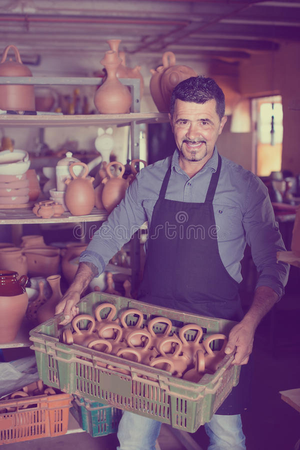 Man potter holding ceramic vessels in atelier. Happy man potter holding ceramic vessels in atelier stock photo