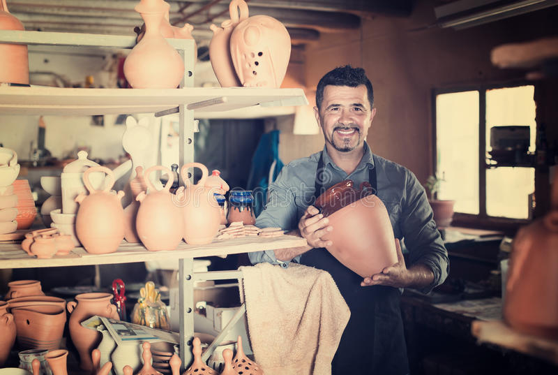 Man potter holding ceramic vessels in atelier. Happy american man potter holding ceramic vessels in atelier stock images