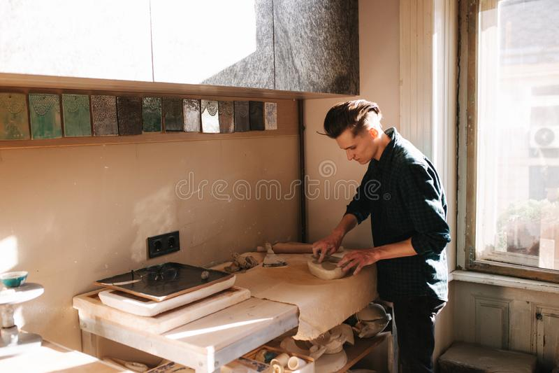 Man potter looking for ware for a work. Young man potter in his workshop. Handsome man work royalty free stock image