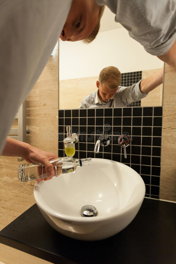 Man poured a bottle of vodka down the sink royalty free stock photos